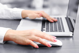 Female hands working on laptop, on grey background
