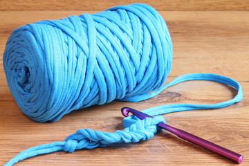 Blue zpagetti t-shirt yarn skein with a purple crochet hook