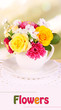 Beautiful bouquet of bright flowers in mug on bright background