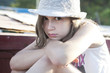 Unhappy little girl in straw hat sitting on chaise longue