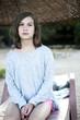 Unhappy little girl sitting on chaise longue on beach