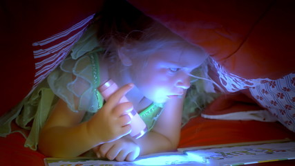 Little girl reading book under covers close up