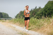 Beautiful blonde woman running along the riverside