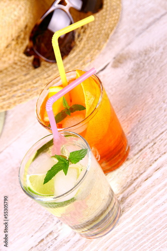Mojito, orange cocktails with straw and holiday background