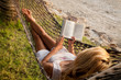 Woman reading in a hammock on the beach - 55306557