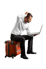 man sitting on suitcase and looking at laptop