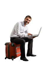 man sitting on suitcase and working