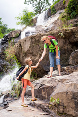 mother and  daughter standing near the waterfall