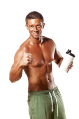 Muscular man holding a plastic bottle and showing thumbs up