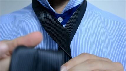 Business man tying a tie