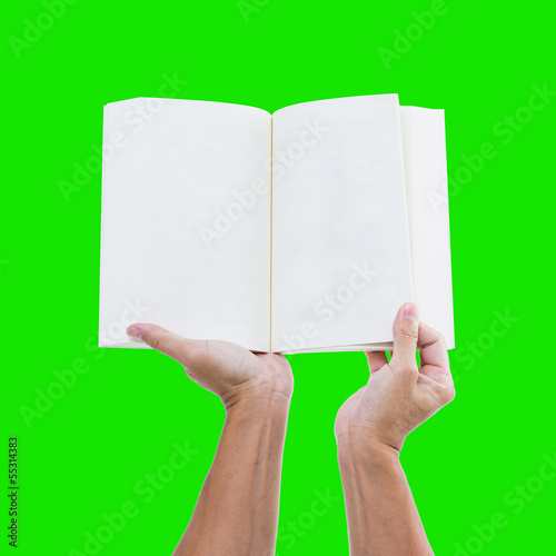 Hand holding blank notebook on green with clipping path