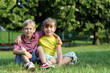 happy little girl and boy sitting on grass