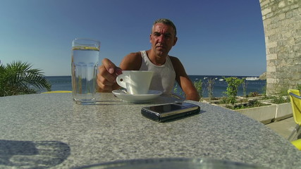 Man Drinking Coffee at a Seaside Beach Restaurant