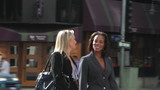 Two Businesswomen Chatting Walking Along Street