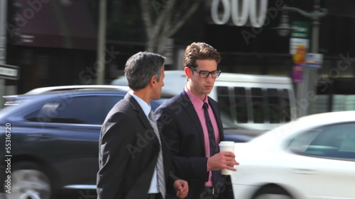 Two Businessmen Chatting Walking Along Street