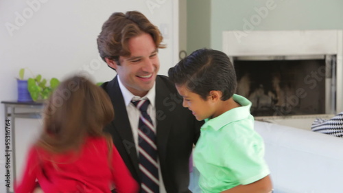 Businessman Home From Work Greeted By Children