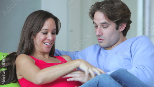 Pregnant Couple Relaxing On Sofa Together