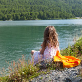 girl on the shore of a mountain lake