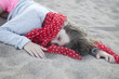 unhappy little girl in straw hat. girl lies on the sand