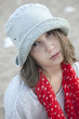 portrait of Unhappy little girl in hat and red scarf in spot