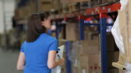 Female Worker With Clipboard In Warehouse