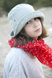 Unhappy little girl in hat and red scarf in spot