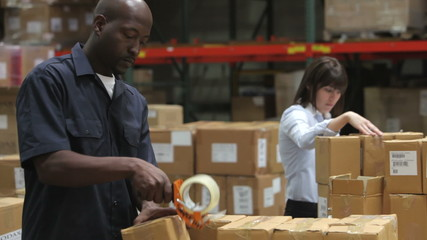 Worker Checks Clipboard As Colleague Seals Boxes