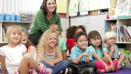 Elementary Age Schoolchildren Sitting On Floor With Teacher