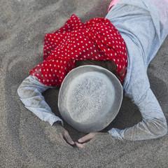 portrait ofunhappy little girl in straw hat. girl lies