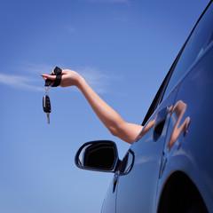 Frau hält Schlüssel aus dem Autofenster