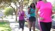 Group Of Women Jogging Down Urban Street