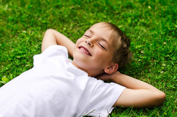 Smiling little boy lying in a field