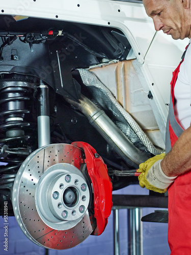 Car mechanic in a garage repairs a bracke