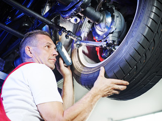 Mechanic in a garage checks a tyre of a car