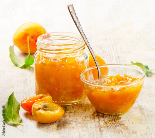 Apricots jam on a wooden table.