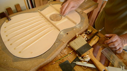 Luthier sanding a guitar in workplace
