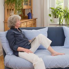 Seniorin sitzt nachdenklich mit tablet-computer auf dem Sofa
