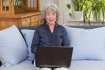 Seniorin sitzt mit Laptop auf dem Sofa