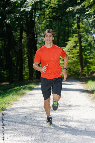 Young man / athlete Running Through Park