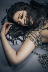 Bondage, beautiful brunette young with silver chains