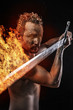 Strong warrior licking a big sword in fire, covered in mud and n