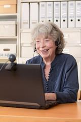 Seniorin sitzt lachend mit Headphone vor ihrem Laptop