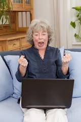 Seniorin schreit wütend ihren Laptop an