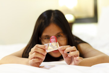 Asia woman opening a condom on her bed.