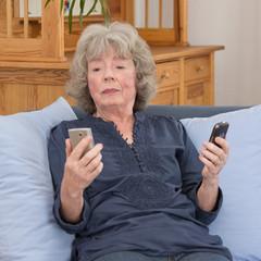 Nachdenkliche Seniorin mit 2 Mobiltelefonen
