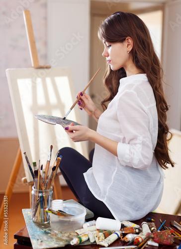 female artist  near  easel with blank canvas