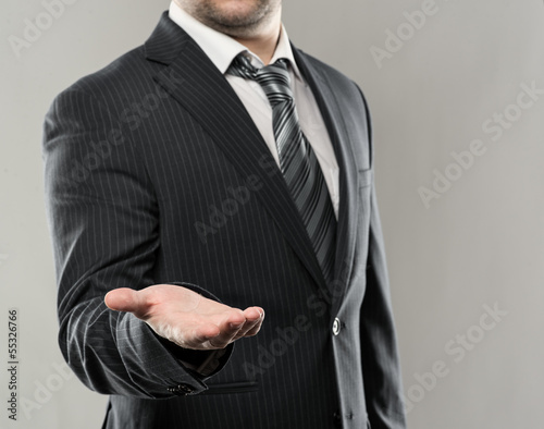 Businessman with open palm offering something
