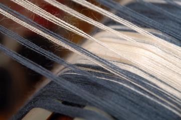 Closeup, blaue und weiße Fäden am Webstuhl