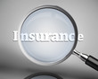 Magnifying glass showing insurance word in white