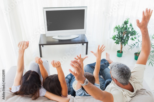 Family raising their arms in front of television